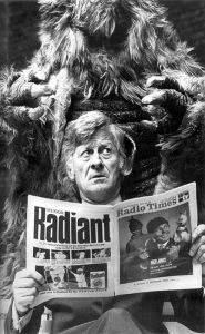 Jon Pertwee reading a paper, sitting in front of a yeti!